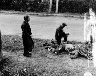 French civilians place flowers on the body of a fallen American soldier, Normandy, summer 1944.