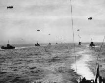 A convoy of infantry landing craft sails across the English Channel toward Normandy, June 6, 1944. Each landing craft is towing a barrage balloon for protection against low-flying German aircraft.