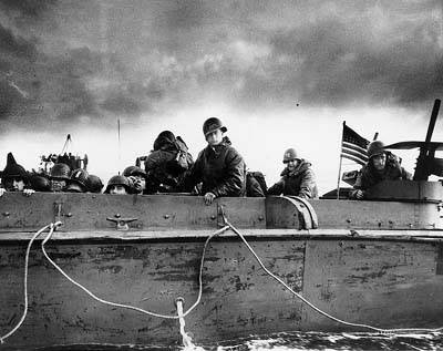 Troops and crewmen aboard a LCVP (Landing Craft, Vehicle, Personnel) as it approaches a Normandy beach, June 6, 1944.