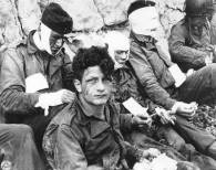 Wounded men of the 3rd Battalion, 16th Infantry Regiment, 1st Infantry Division, on Omaha Beach, June 6, 1944.