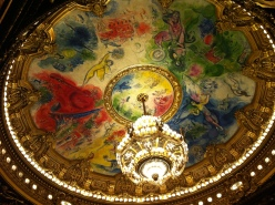The 8-ton chandelier, which hangs 65 feet above the Auditorium, illuminates a ceiling masterpiece painted by Marc Chagall.