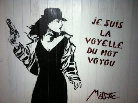 Miss.Tic. Je suis la voyelle du mot voyou (I am the vowel of the word thug). Spray paint on fence. 2012. Created for exhibition, L'Adresse Musée de la Poste, Paris.