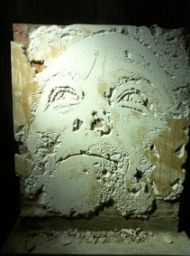 Vhils. Scratching the surface series 4. Brick wall covered in cement and plaster, carved with jackhammer, chisel and box cutter. 2012. Created for exhibition, L'Adresse Musée de la Poste, Paris.